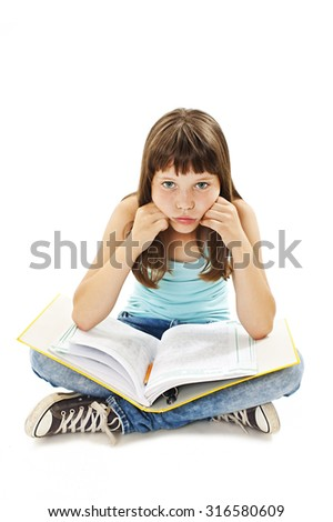 Tired school girl, frustrated and overwhelmed by studying homework. Young girl sitting down on floor isolated on white background.  - stock photo