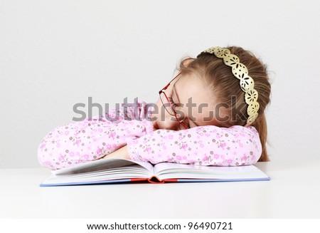 Tired schoolgirl sleeping on book instead of learning - stock photo
