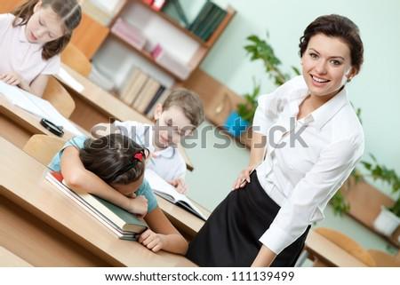 Tired schoolgirl sleeps at the school desk - stock photo