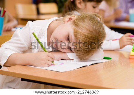 tired schoolgirl writes in a notebook during lesson - stock photo