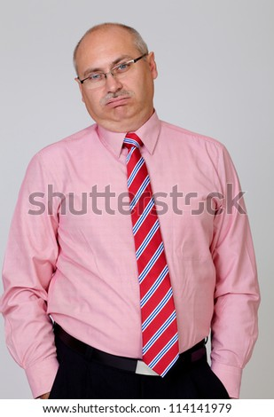 Tired senior businessman in a shirt and tie with hands in the pockets isolated on grey - stock photo
