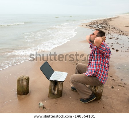 Tired senior businessman sitting with notebook on beach