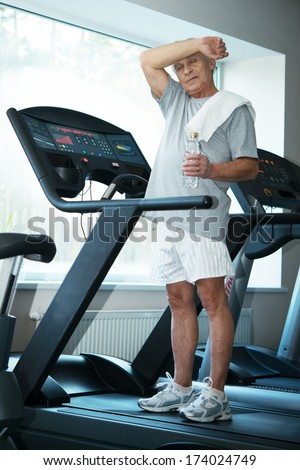 Tired senior man on a treadmill with towel and bottle of water - stock photo