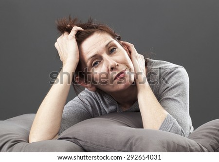 tired senior woman resting her face and hands laying down on cushions for comfort and relaxation - stock photo