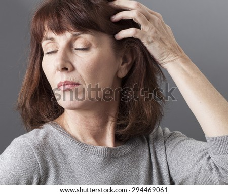tired senior woman wearing a grey sweater taking care of her hair, closing eyes for relaxation, showing her aging lines