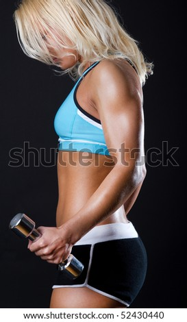 Tired sexy athlete with dumbbells in gym