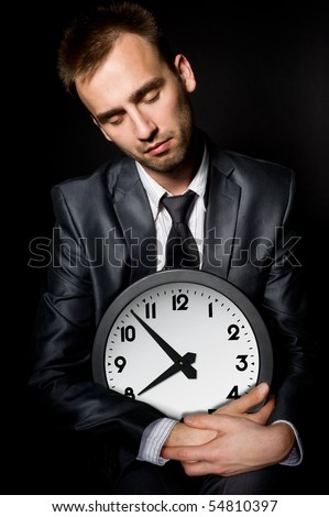 tired sleeping businessman holding clock, over black - stock photo