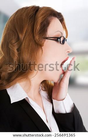 Tired sleepy beautiful businesswoman yawning - stock photo