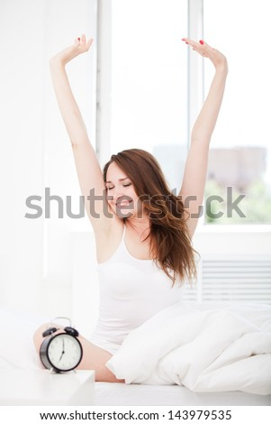 Tired sleepy woman waking up and giving a stretch while sitting in bed at home - stock photo