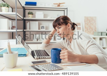 Tired sleepy woman working at office desk and holding a cup of coffee, overwork and sleep deprivation concept