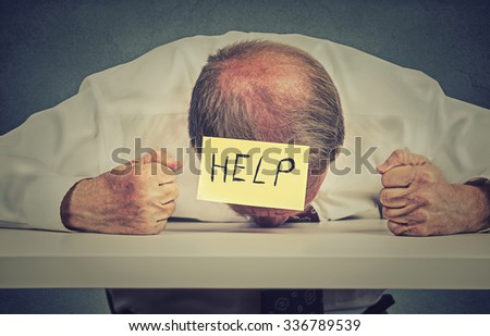 Tired, stressed senior employee needs help. Frustrated elderly man in formal wear with note on his forehead leaning his head on the table exhausted. Long working hours, aging concept  - stock photo