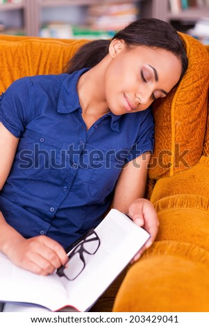 Tired student. Beautiful African female student sleeping in armchair while holding a book  - stock photo