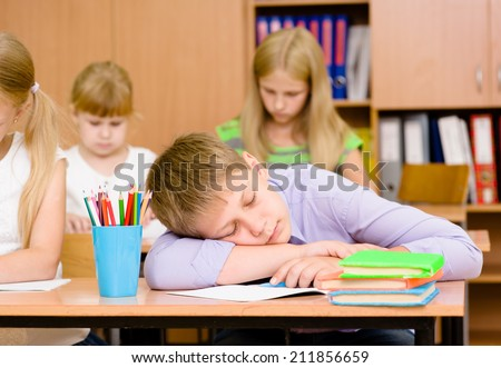 tired student boy sleeping in classroom
