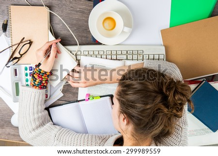 tired student girl with books and coffee sleeping on the table. overnight preparing for the exam . studying hard. Top view - stock photo