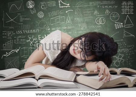 Tired student girl with glasses sleeping on the books in the library - stock photo