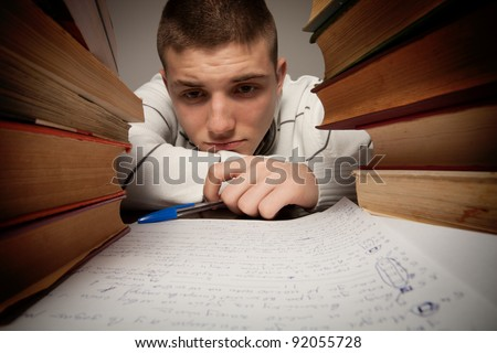 Tired student having a lot to read - stock photo