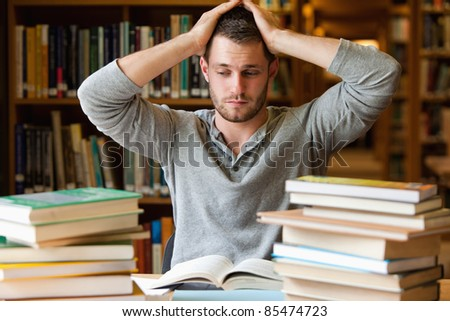 Tired student having too much to do in a library - stock photo