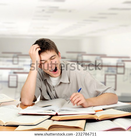 Tired Student is Yawning at the School Desk in the Classroom - stock photo