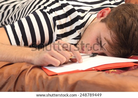 Tired student resting in the bed of his bedroom while he was working - stock photo