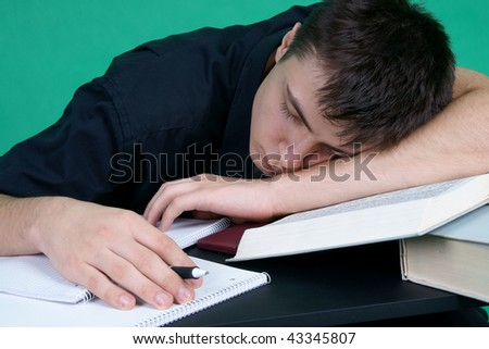Tired student sleeping at the desk - stock photo