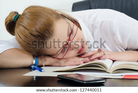 Tired student sleeping on the books instead of studying. - stock photo
