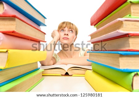 Tired student woman sitting at the desk surrounded with piles of books . Isolated