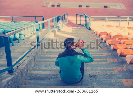 tired sweaty athlete drinking water at the stadium on the stairs (intentional vintage color) - stock photo