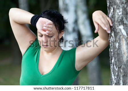 Tired sweaty overweight woman catching her breath after training