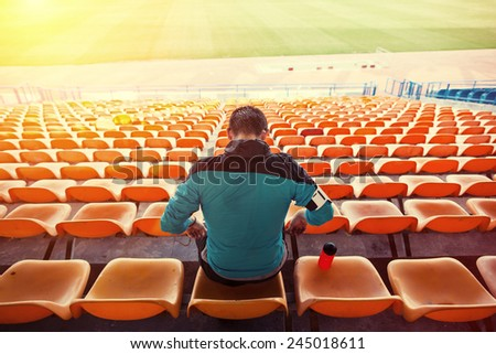 tired sweaty sportsman sitting on the chairs at stadium with sun shining - stock photo