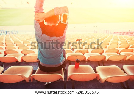 tired sweaty sportsman sitting on the chairs at stadium with sun shining and flare - stock photo