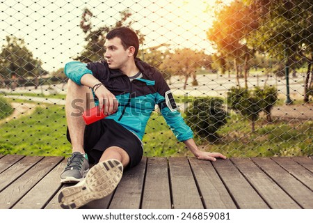 tired sweaty sportsman sitting on the wooden floor in the park with red plastic sport bottle  - stock photo