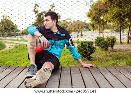 tired sweaty sportsman sitting on the wooden floor in the park with red plastic sport bottle and looking far away - stock photo