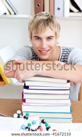 Tired teeenager sleeping in a library after studying long time - stock photo