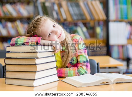 Tired teen girl in library - stock photo