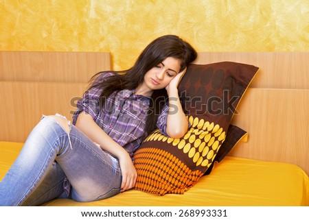Tired teenage girl falling asleep in the bedroom - stock photo