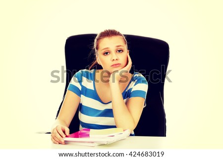 Tired teenage woman sitting behind the desk - stock photo