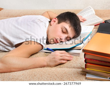 Tired Teenager sleep on the Sofa with the Books