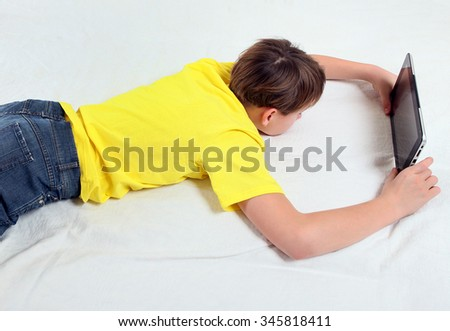 Tired Teenager with Tablet Computer on the Bed - stock photo