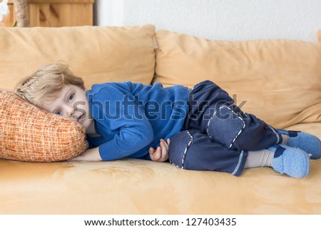 Tired toddler boy laying on couch at home