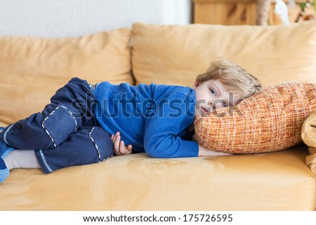 Tired toddler boy laying on couch at home, indoors