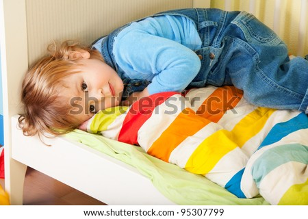 Tired toddler laying in his bed on a stripped blanket - stock photo