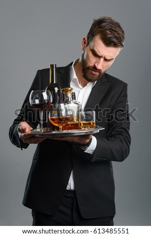 Tired waiter holding full tray of drinks. There are variety of glasses and alcoholic beverages on the metal dish. Vertical portrait of well-dressed man with frowning face on gray.