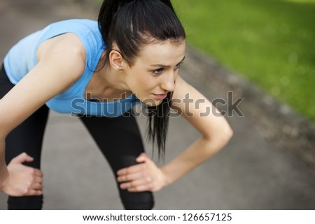 Tired woman after jogging - stock photo