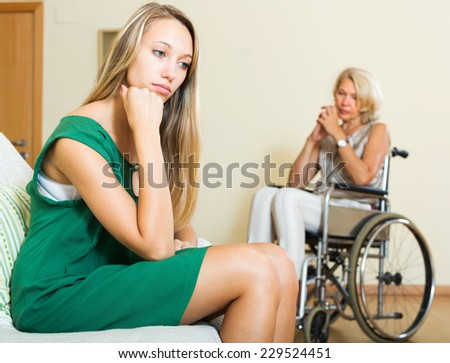 Tired woman and mature disabled person on chair indoor - stock photo