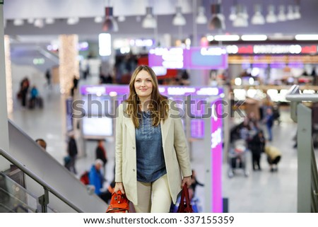 Tired woman at international airport walking through terminal. Happy passenger at stairs. Canceled flight due to pilot strike. - stock photo