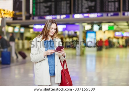 Tired woman at international airport walking through terminal. Upset business passenger waiting. Canceled flight due to pilot strike. - stock photo