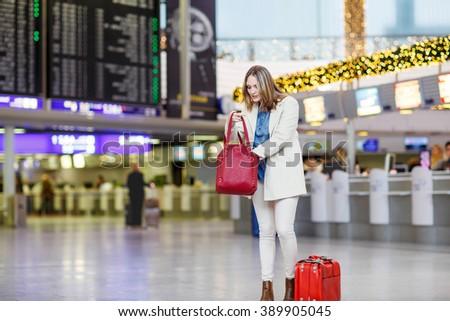 Tired woman at international airport walking through terminal. Upset business passenger waiting. Canceled flight due to pilot strike. Paris, France. - stock photo