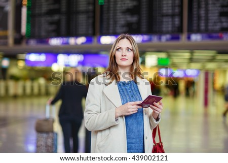 Tired woman at international airport walking through terminal. Upset female tourist passenger waiting. Canceled flight due to pilot strike. - stock photo