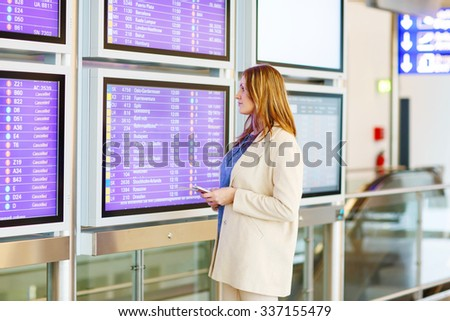Tired woman at international airport with tickets and passport checking mobile for flight. Angry passenger waiting. Canceled flight due to pilot strike. - stock photo