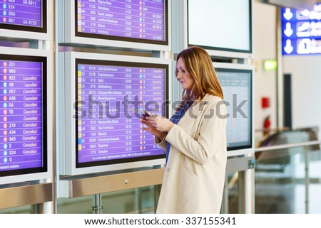 Tired woman at international airport with tickets and passport checking mobile for flight. Annoyed passenger waiting. Canceled flight due to pilot strike. - stock photo